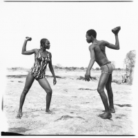 friends fighting with stones, 1976, hand printed fiber base silver gelatin print